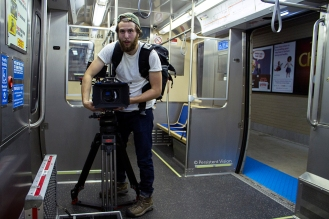 1st AC, Jonathan Sherman, setting up the RED camera on set aboard the CTA