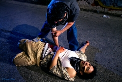 Juan (Eddie Martinez) trying to stop Cesar's (Karman Bajuyo) bleeding wound