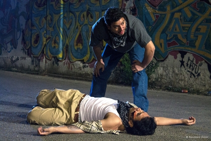 Juan (Eddie Martinez) keeps a look-out as Cesar (Karmann Bajuyo) lies on the ground hurt and wounded
