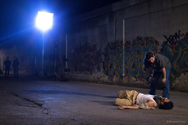 Director, Kaveh Ryndak watches from afar as Eddie Martinez (Juan) and Karmann Bajuyo (Cesar) run through the scene